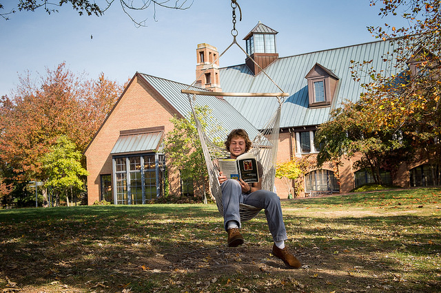 a SMCM student sitting on a hammock reading a book outside one of the college buildings
