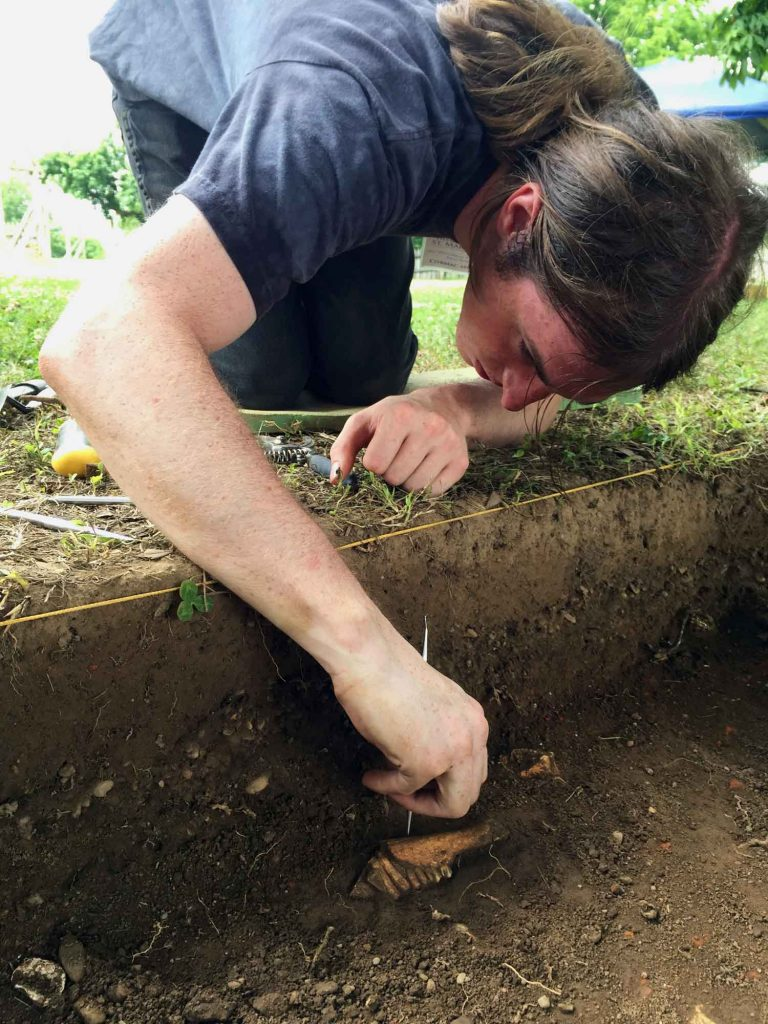 A male student digs in the dirt unearthing historical artifacts