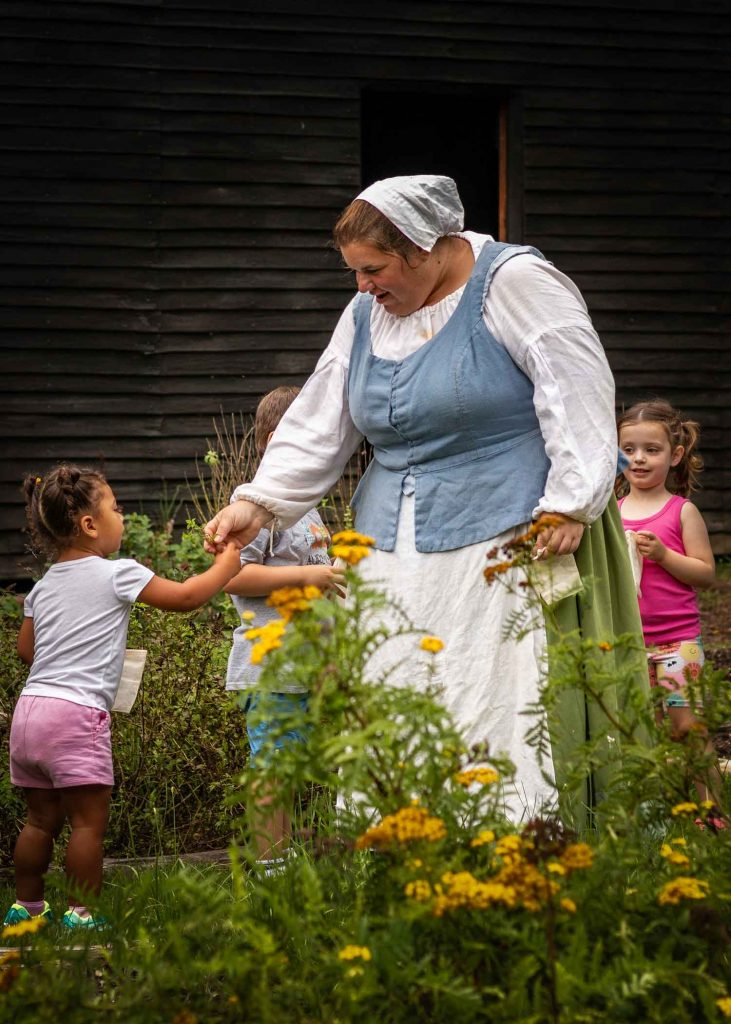A woman dressed in historical costume hands a flower to a young girl