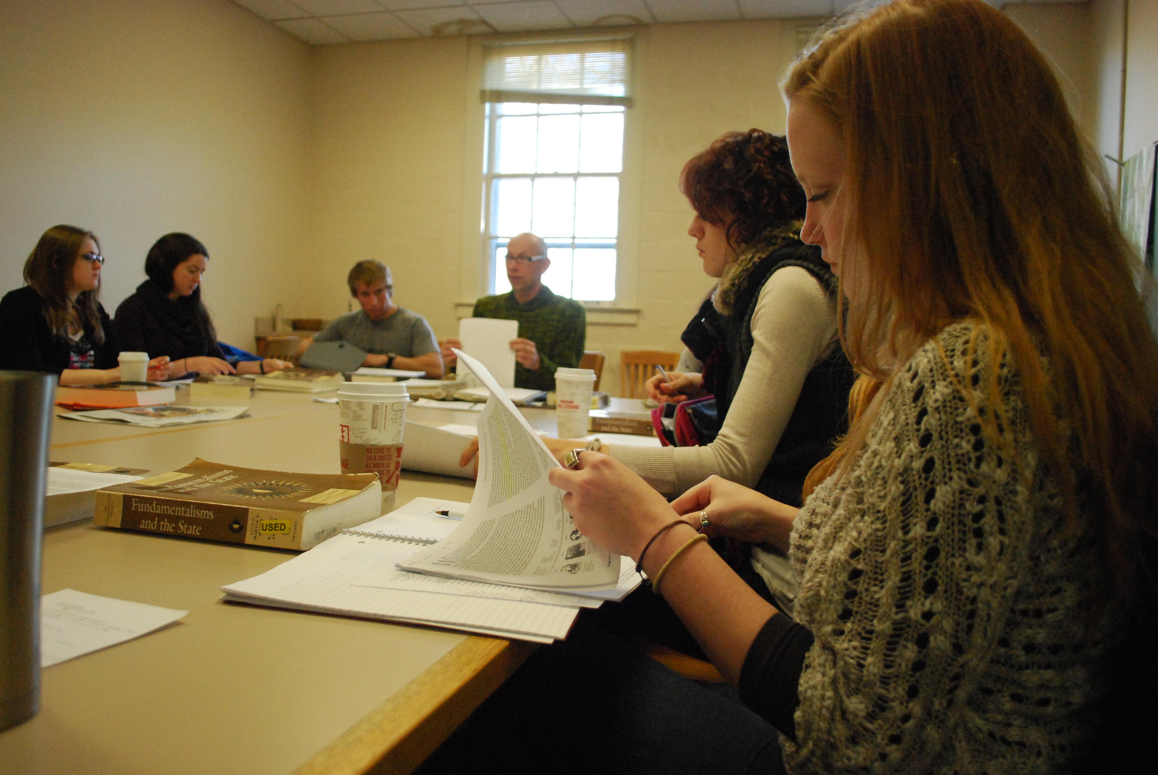 Professor Bjorn Krondofer teaches a political sutides class at a table with his students.