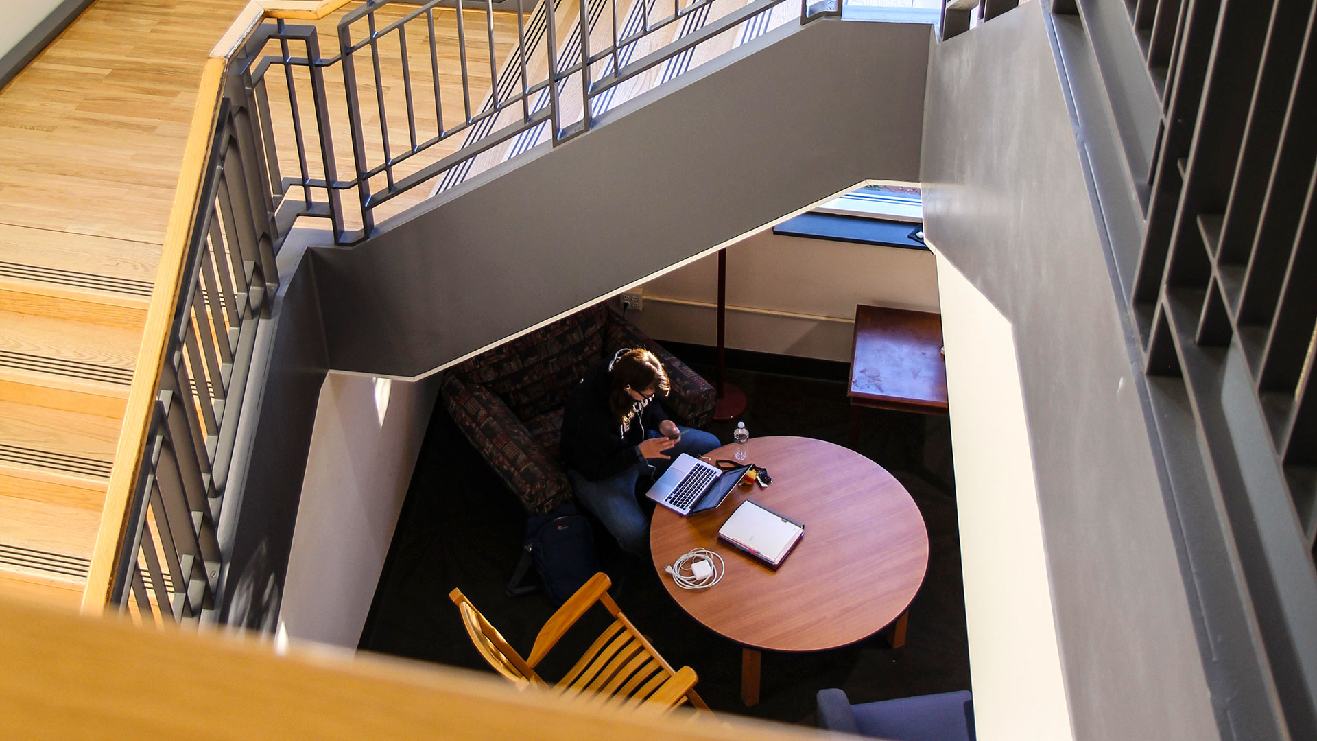 An SMCM student can be seen in the study nook under the 3rd floor stairs in the Hilda C. Landers Library
