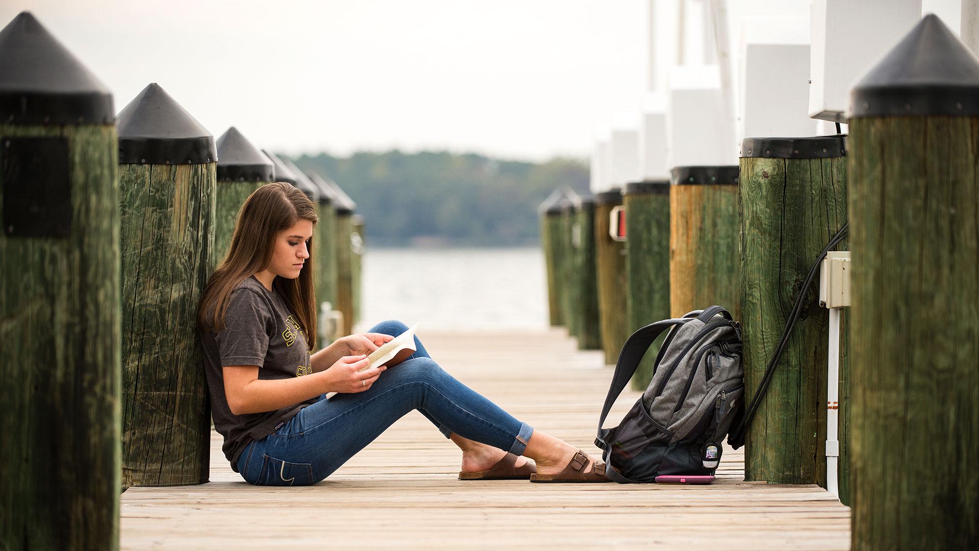 SMCM student studies on the riverfront dock.