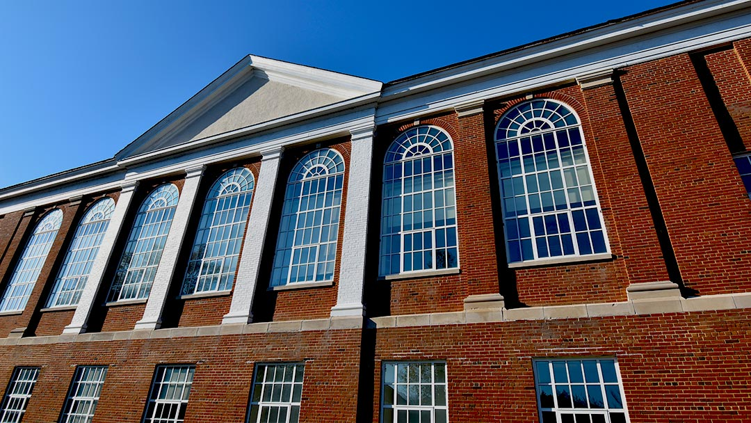SMCM Kent Hall architectural detail photo of brick facade and window on a blue sky sunny day