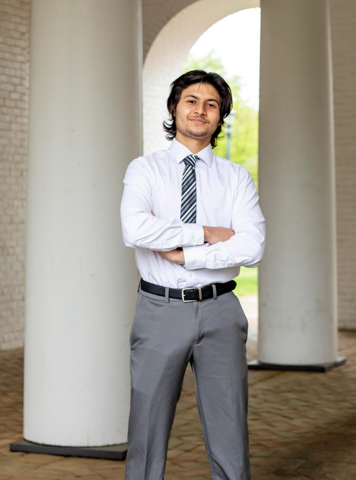 Male student dressed in a suit stands in a historical breezeway with arms crossed
