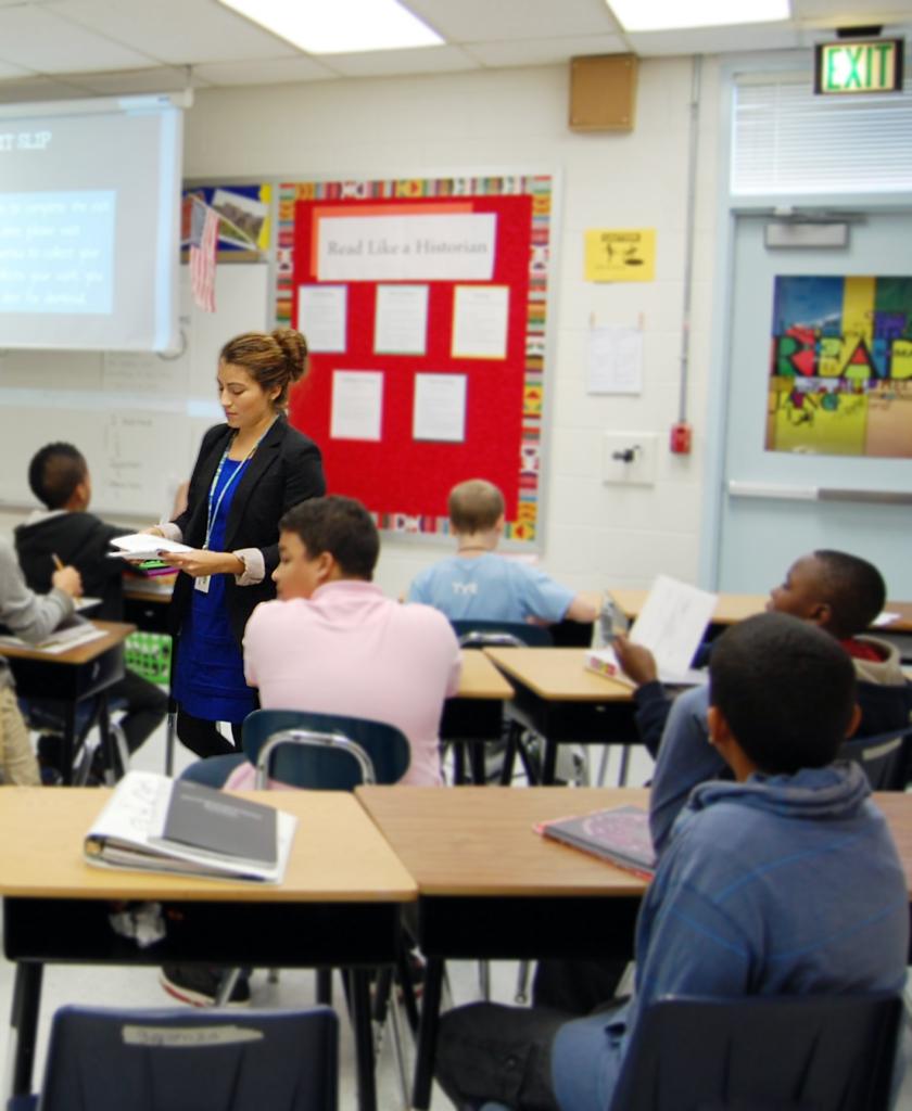 A student teacher walks through an elementary classroom.
