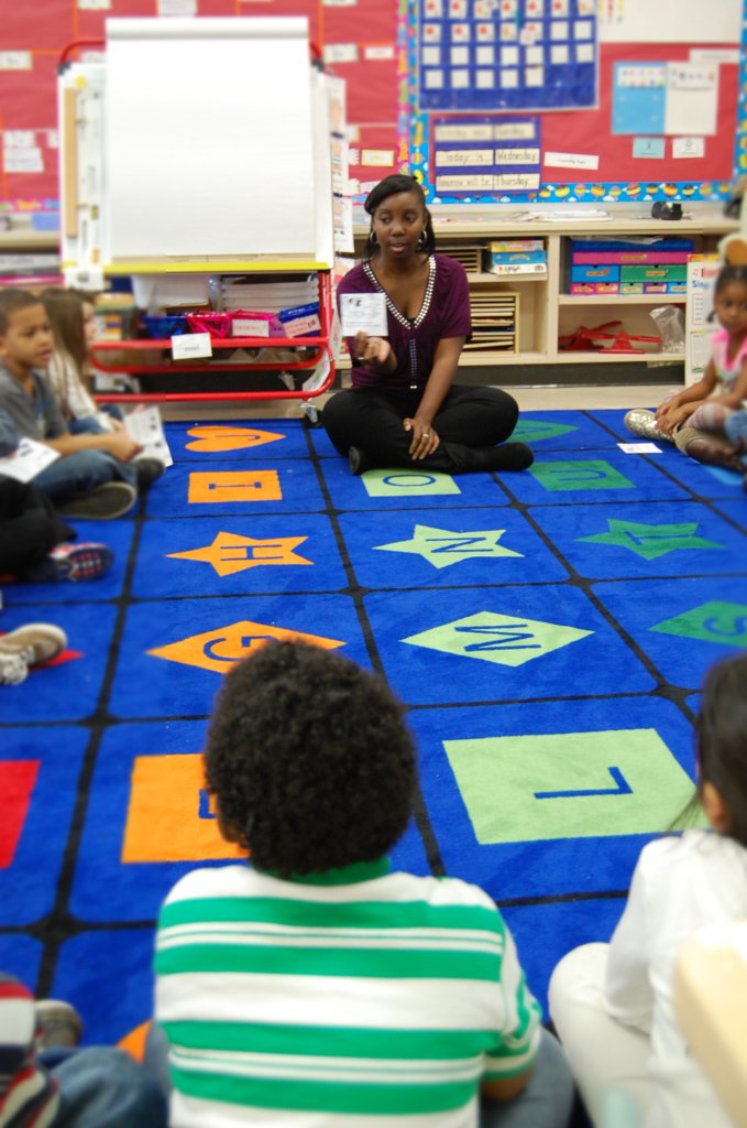 Students sit in a circle and the student teacher holds something up for the class to see