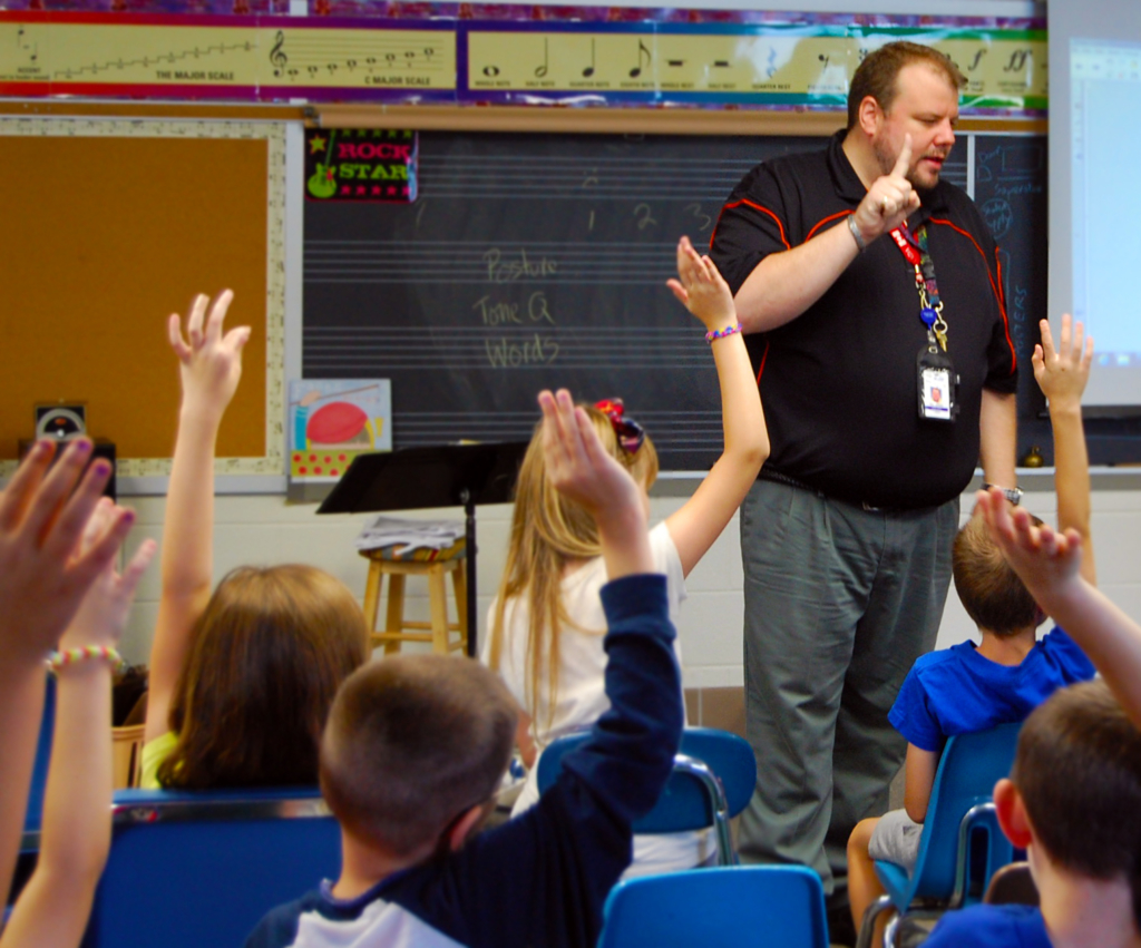 A student teacher asks the class a question and many students raise their hands.