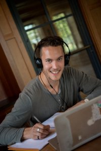 a student wearing headphones smiles at the camera while doing schoolwork