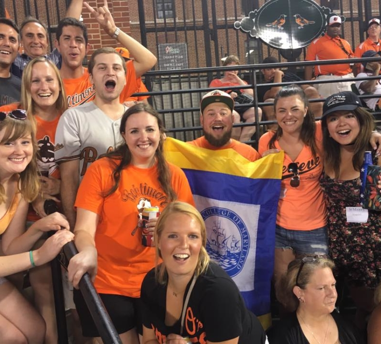 Alumni at Camden Yards in Orioles gear and holding SMCM flag