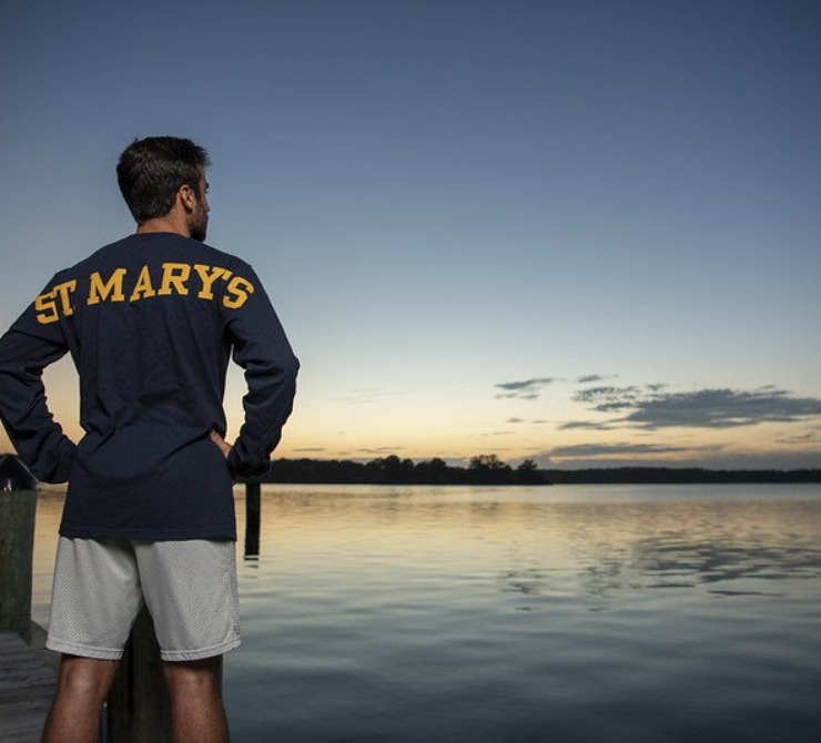 Student wearing St. Mary's logo shirt facing away from the camera, looking towards the water