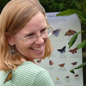 Laura M. Ahearn in front of butterfly pictures