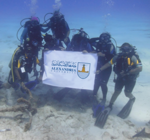 The Maritime Archaeology in Department of Archaeology and Greco-Roman Studies, Alexandria University group posing underwater while holding up the Alexandria University banner