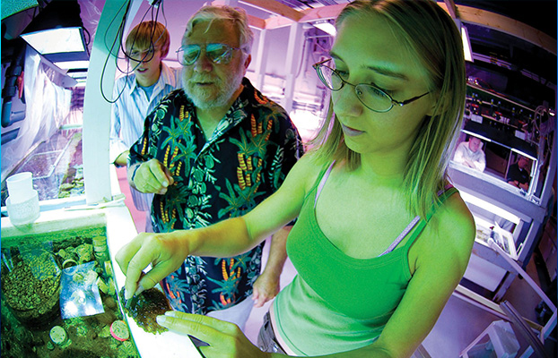 Two students and a teacher inspect marine life in a classroom.