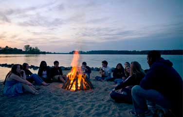students sitting around a bonfire on a beach