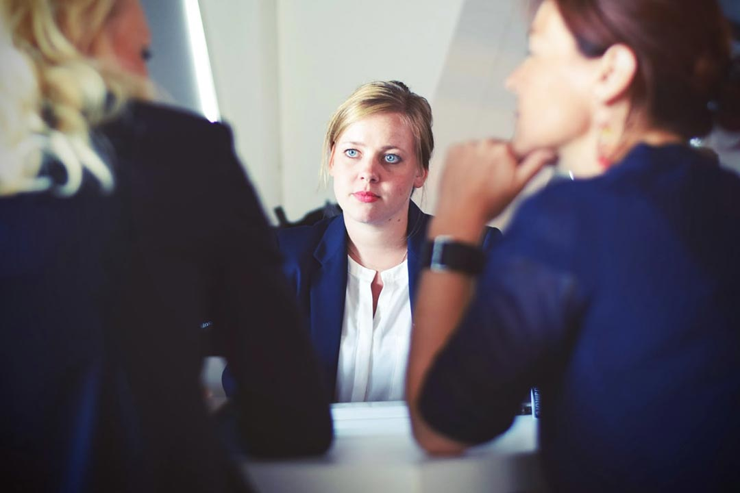 interview photo illustration: Interviewers in foreground, focus on candidate in center