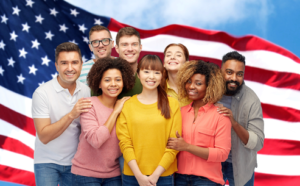 A group of diverse people posing in front of the American flag