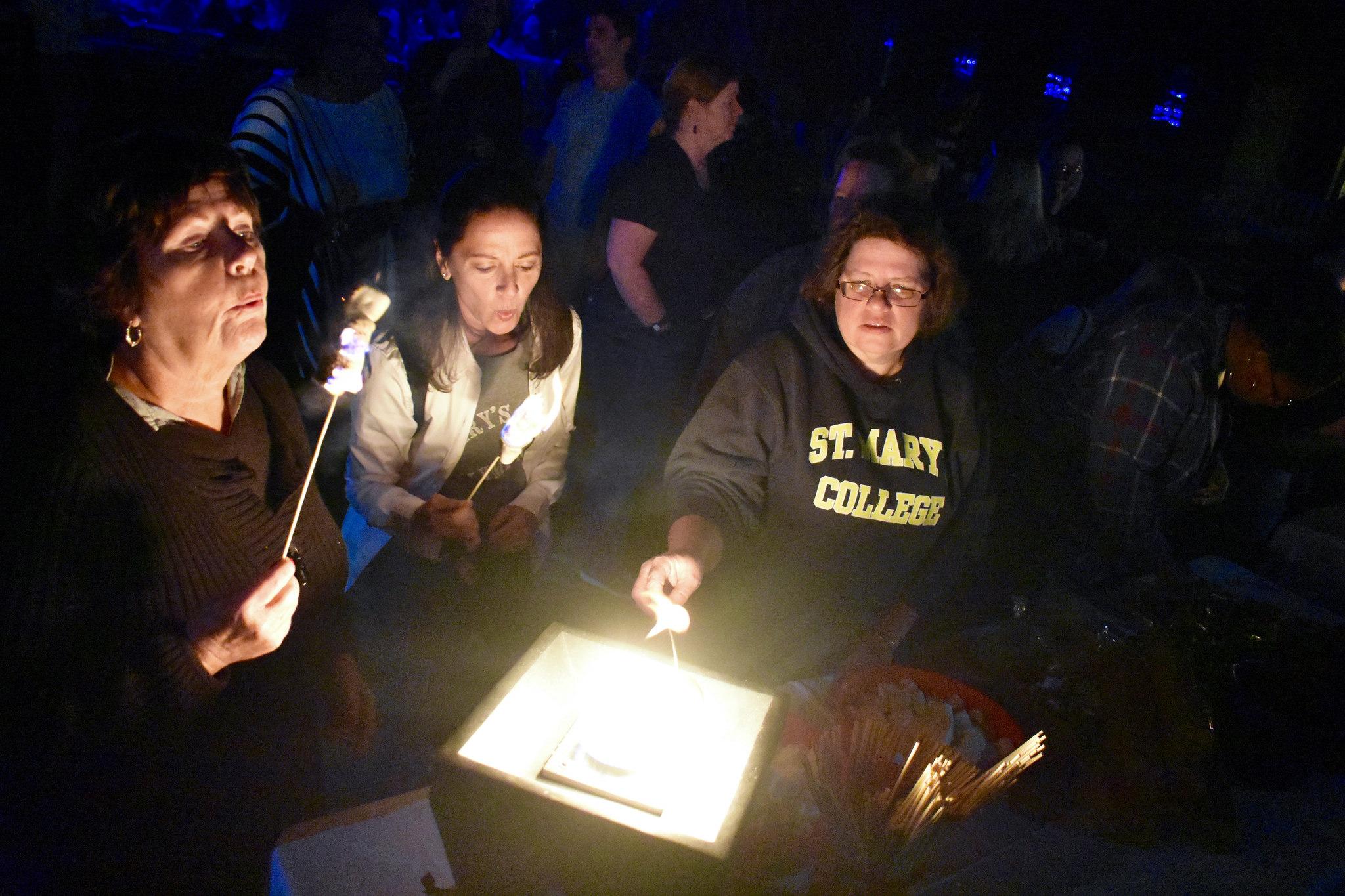 Three women making s'mores at Hawktoberfest