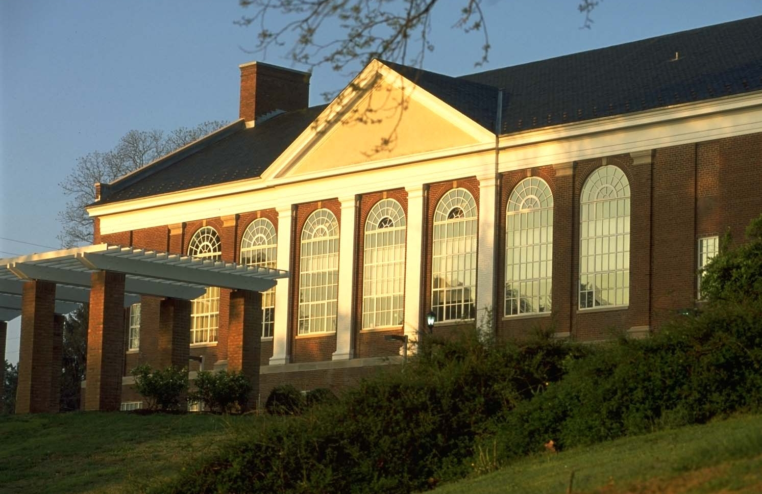 A historic brick building with white columns surrounded by grass.