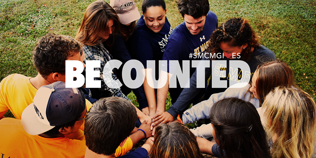 Group of students put their hands into a huddle with text over their hands: #smcmgives Be Counted on November 28, 2017