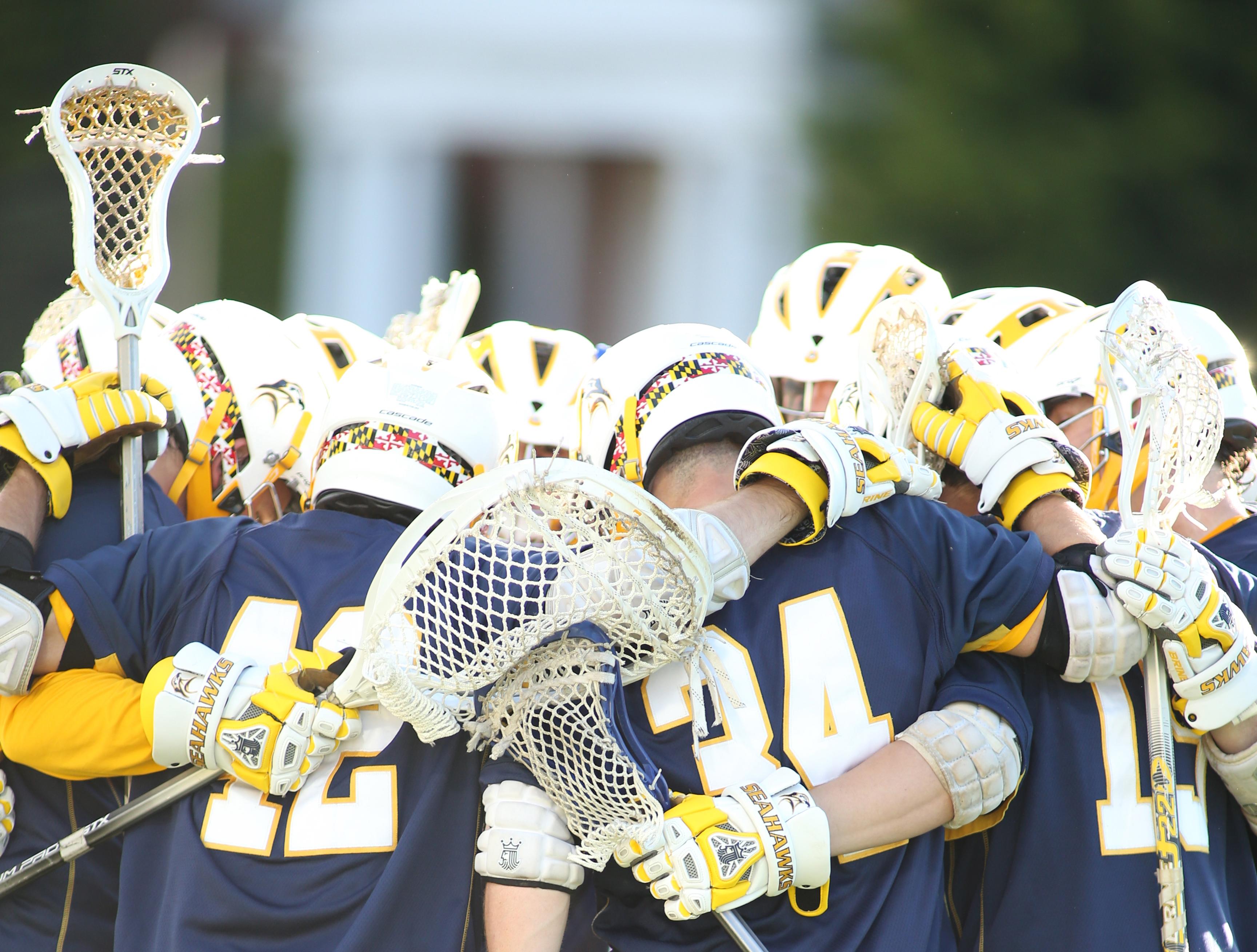 Men's Lacrosse team in a huddle