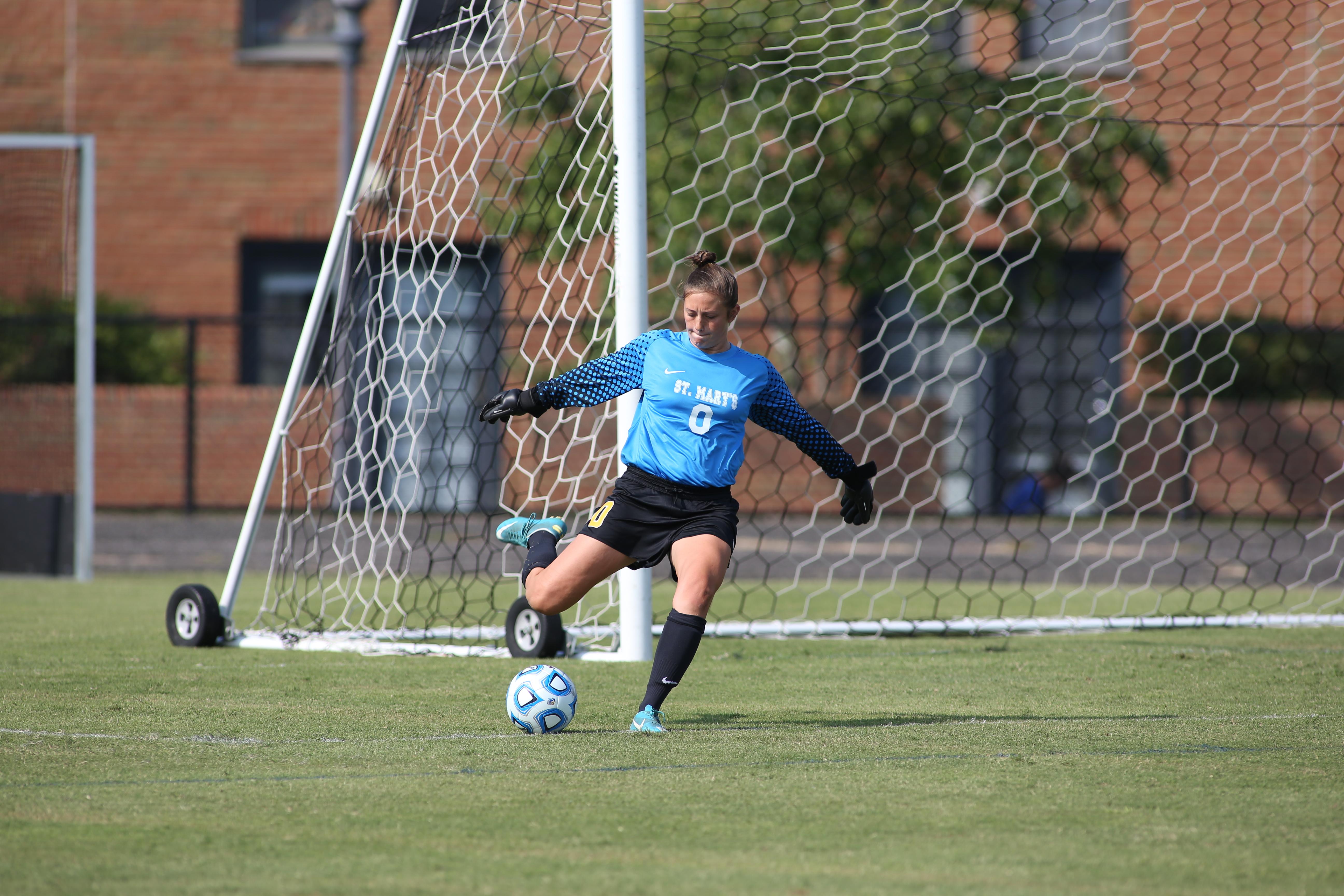 A SMCM Women's Soccer goalie kicking a ball