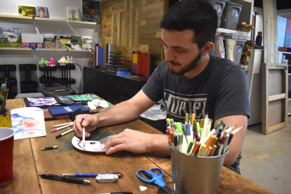 A male student makes an art project with colored pencils in an art studio.