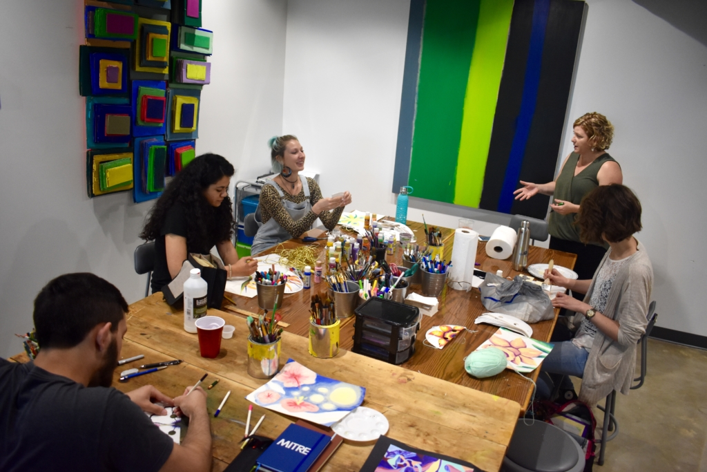 Four St. Mary's College interns work in a colorful art studio, drawing and painting.