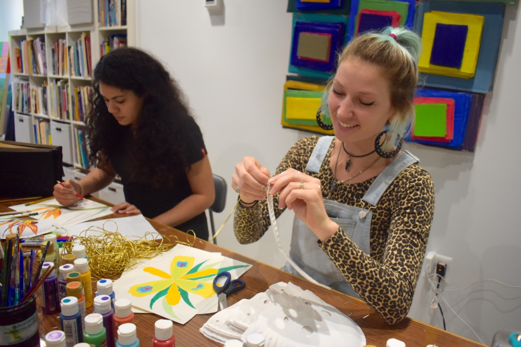 Two female St. Mary's College students work in an art studio with paint and fabric.