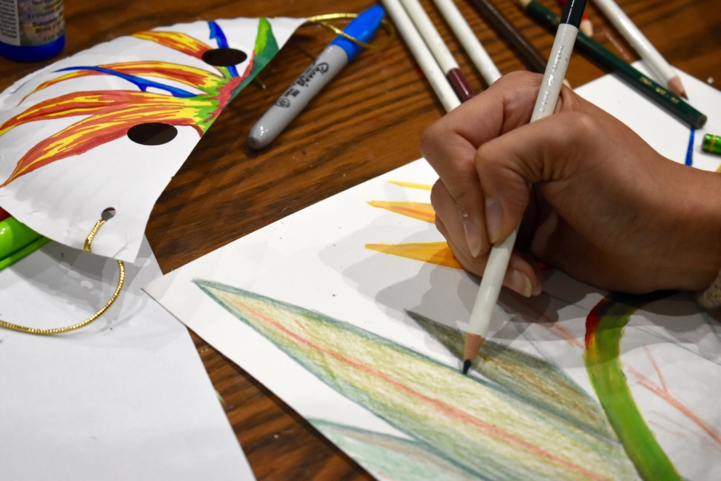 A picture of someone drawing a picture with colored pencils on a wooden art table.