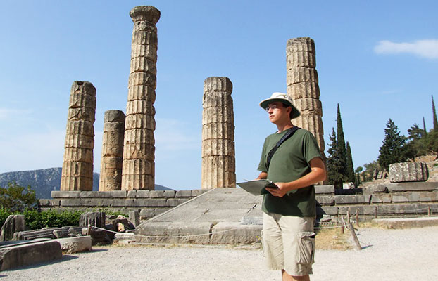 a student standing behind an historical structure in Greece.