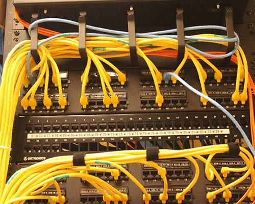 Image of cables in ports within a network switch closet.