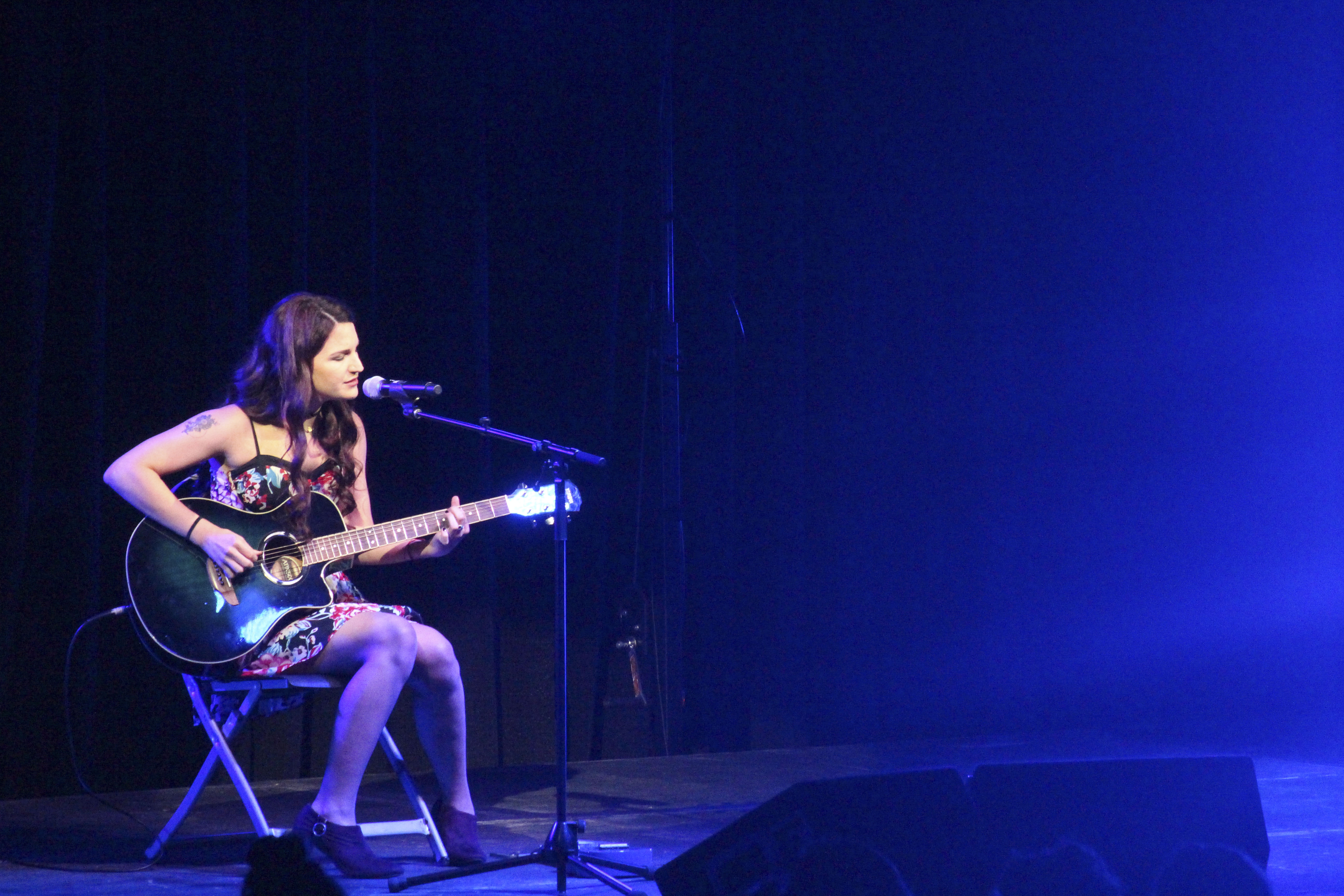 A student playing guitar on stage
