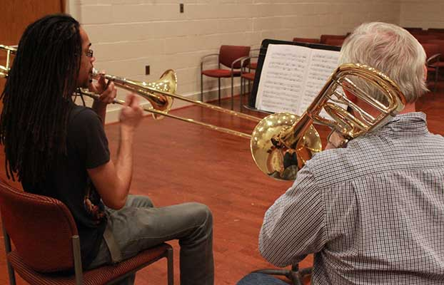 a student and instructor playing the trumpet together.
