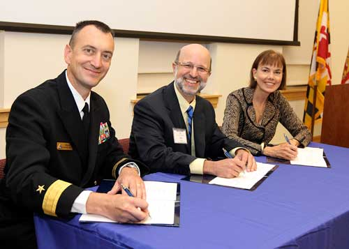 Photo by Darren Farrell: Rear Admiral Randy Mahr, Commander, Naval Air Warfare Center Aircraft Division; Joseph Urgo, St. Mary's College president; and Bonnie Green, executive director, The Patuxent Partnership, at signing ceremony on October 18.