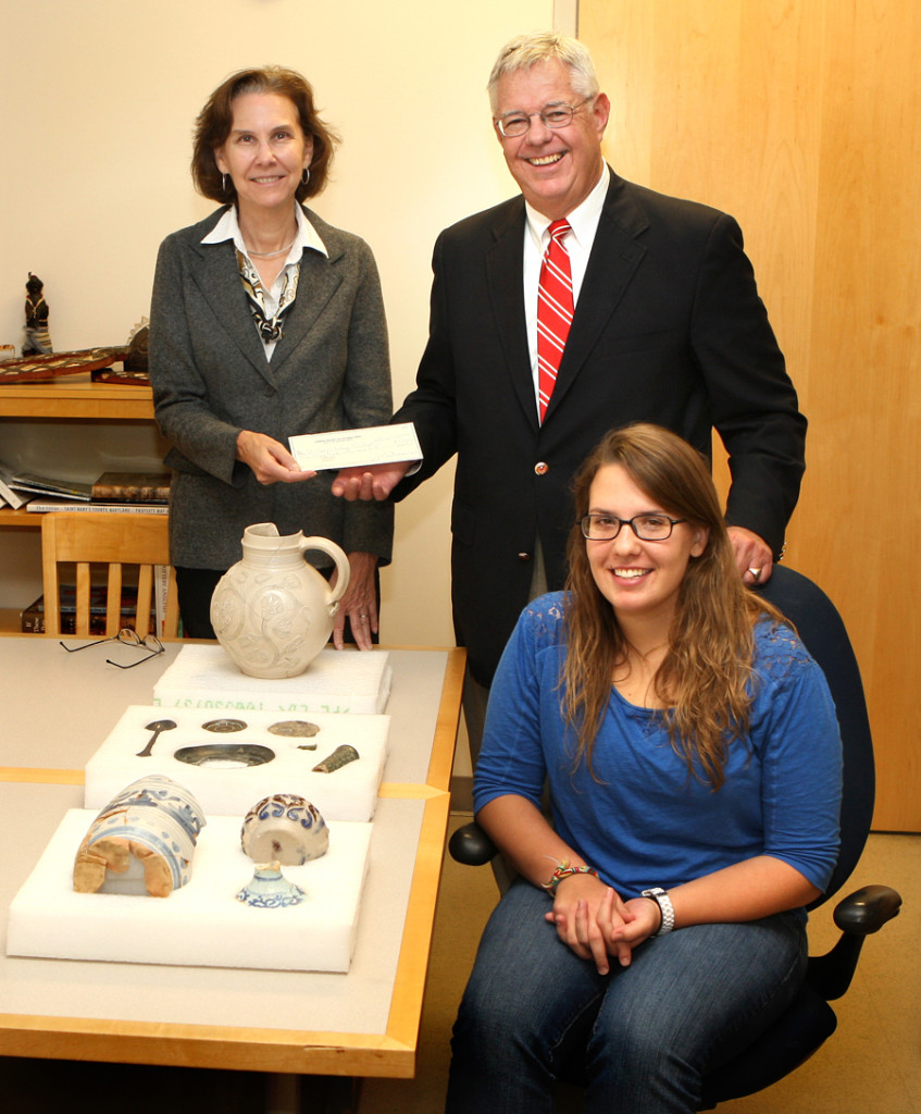 Julia King, associate professor of anthropology, is presented with a donation by James J. Winn Jr., governor of the Society for Colonial Wars. Exhibit creator Jessy Schroeder is seated in front.