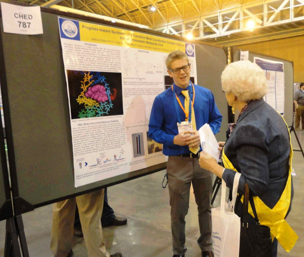 Josh Olexa explains his poster to a judge, a former president of the American Chemical Society