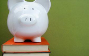 White ceramic piggy bank atop book