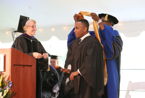 President Jordan confers honorary degree to Commencement speaker Rashad Robinson.