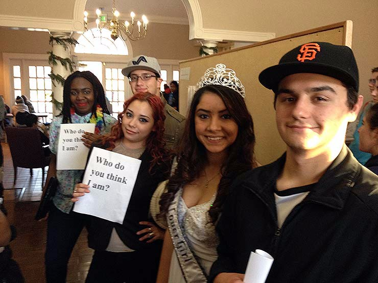 "Five students as the Core 101 Fall Festival holding signs stating ""Who do you think I am?"""