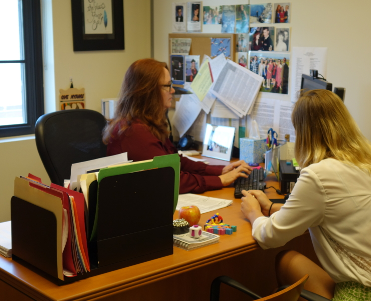 Deirdre Bulger at her desk assisting a female student at St. Mary's College of Maryland.