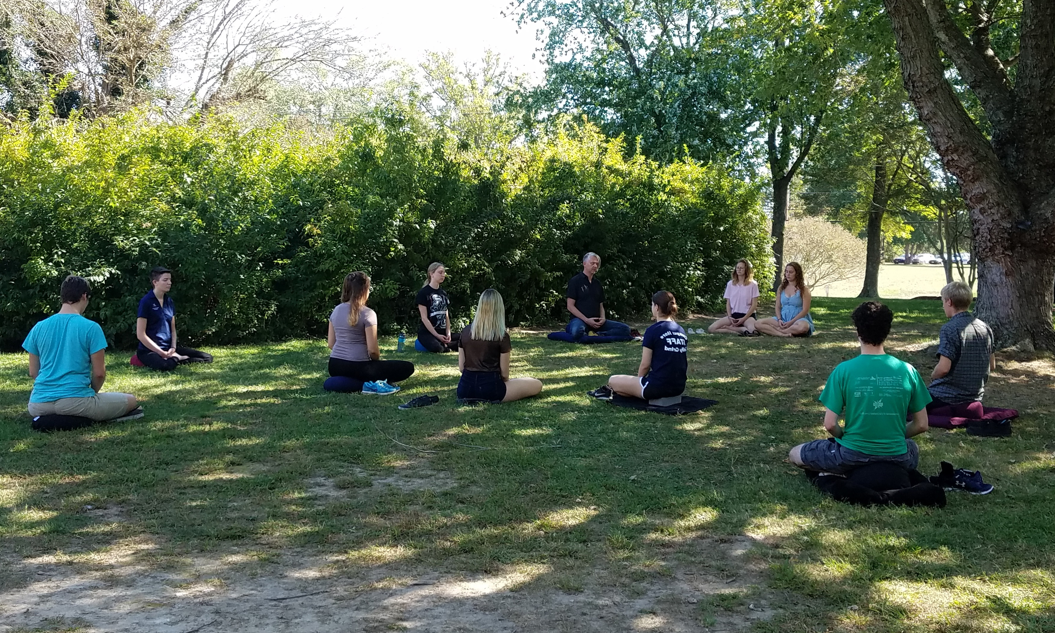 a class meditates outside