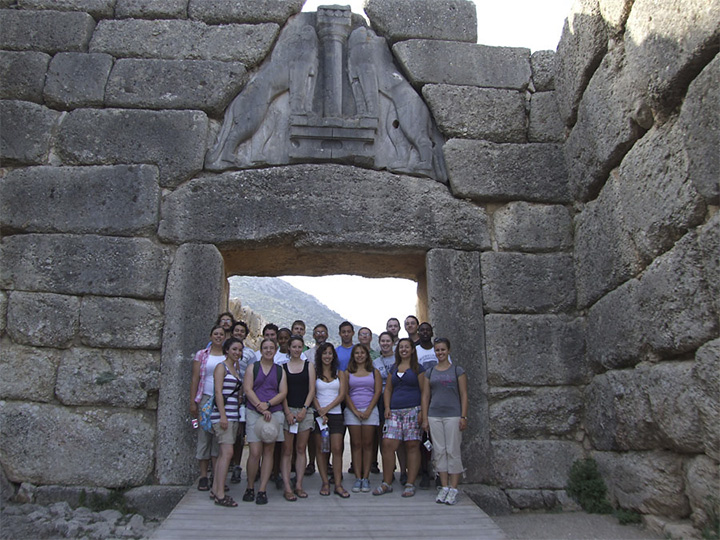 A group of students stand beneath a stone arch with two lionesses carved within.