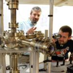 Student and professor examine vacuum chamber