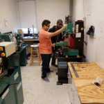 Students work the mill in the machine shop