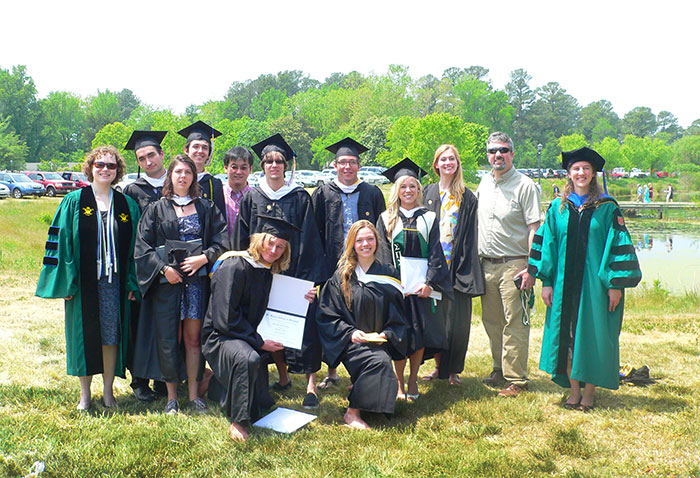 Thirteen students wearing cap and gown and holding their diplomas.