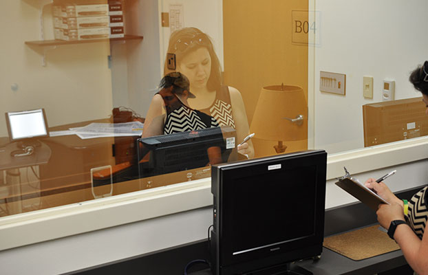 a psychology student standing in an office behind glass.