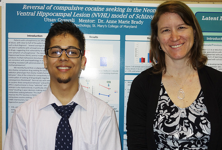 Professor and student standing in front of a poster