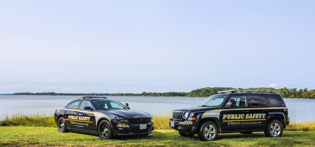 a photo of two smcm public safety vehicles parked outside of the St. Mary's River