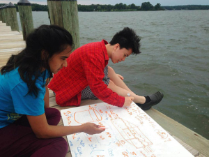 Two students work on their math project on a dock by the water