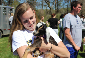 St. Mary's student holds a goat on campus